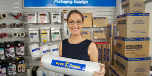 woman holding bubble wrap in a room full packaging supplies